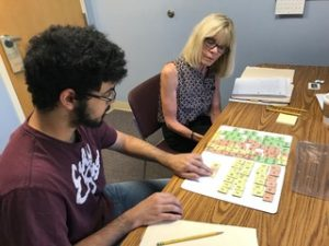 Student working with letter titles with his literacy teacher. You can help students fight illiteracy.
